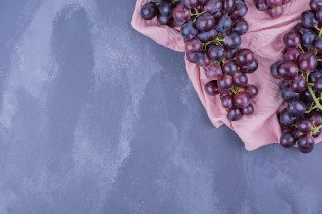 Cachos de uva vermelha em um pedaço de toalha rosa.