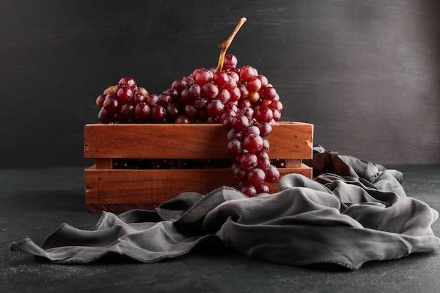 Cachos de uva vermelha em uma bandeja de madeira com fundo preto.
