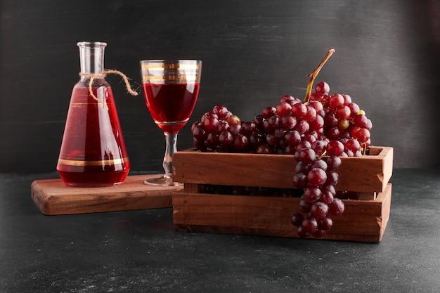 Cachos de uva vermelha em uma bandeja de madeira com uma taça de vinho no preto.