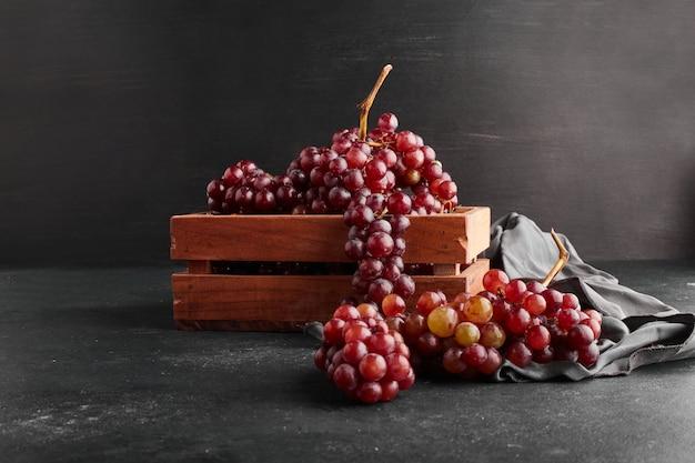 Cachos de uva vermelha em uma bandeja de madeira na superfície preta.