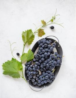 Cachos de uvas azuis em um prato sobre um fundo claro