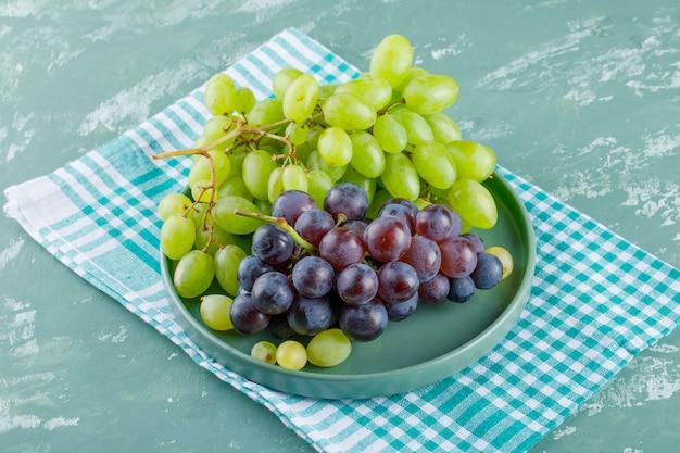 Cachos de uvas em uma bandeja com vista de alto ângulo sobre fundo de gesso e pano de piquenique