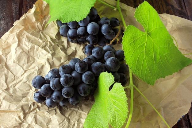 Cachos de uvas frescas, com galhos e folhas, no papel, na mesa de madeira rústica
