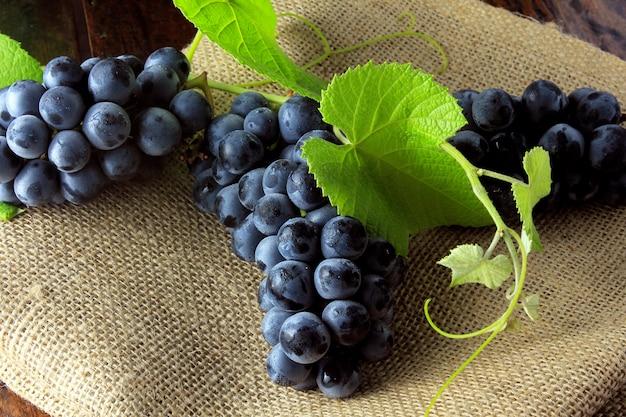 Cachos de uvas frescas, com ramos e folhas, em tecido rústico, na tabl de madeira rústica