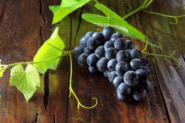 Cachos de uvas frescas com ramos e folhas na mesa de madeira rústica, close-up