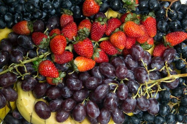 Cachos de uvas, morangos vermelhos e banana fatiada, vista superior. fundo de frutas.