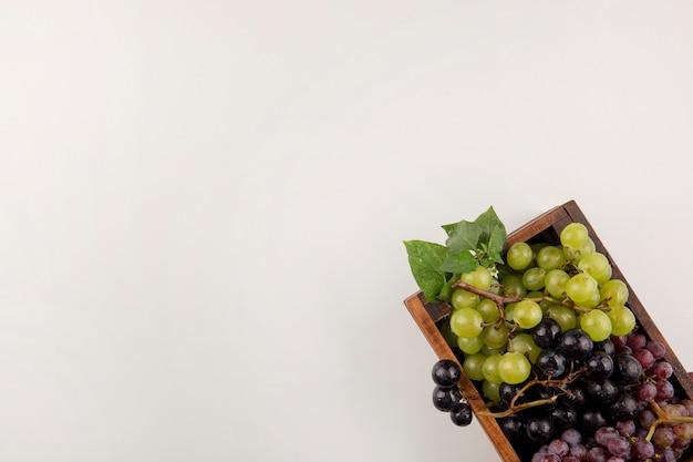 Cachos de uvas verdes e vermelhas em uma caixa de madeira no canto