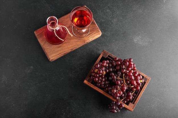 Cachos de uvas vermelhas em uma bandeja de madeira com uma taça de vinho, vista de cima.