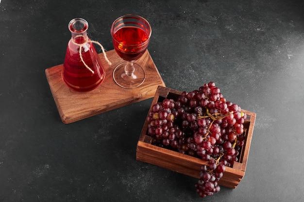 Cachos de uvas vermelhas em uma bandeja de madeira com uma taça de vinho.