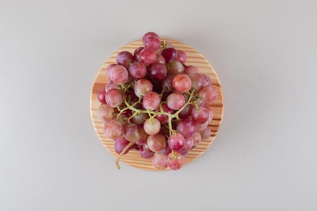 Cachos de uvas vermelhas em uma travessa de madeira sobre mármore