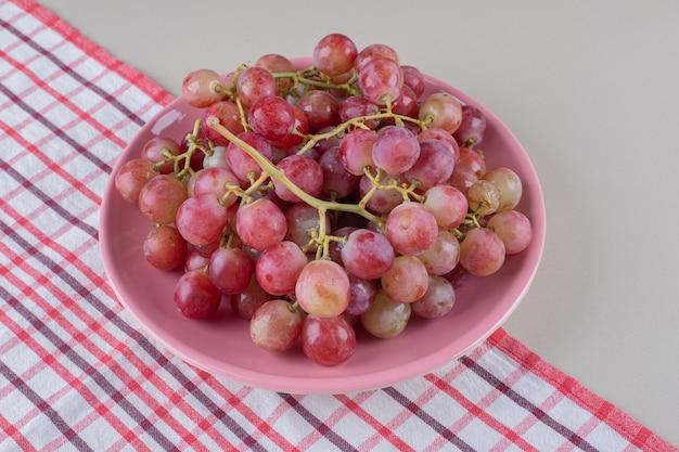 Cachos de uvas vermelhas em uma travessa rosa sobre uma toalha, em mármore
