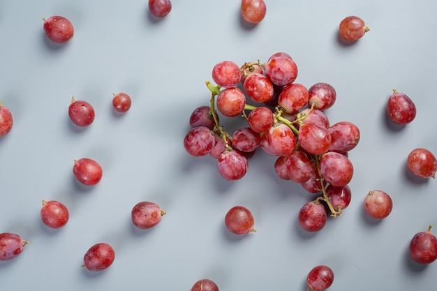 Cachos de uvas vermelhas maduras frescas na superfície azul.
