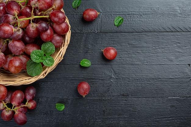 Cachos de uvas vermelhas maduras frescas na superfície de madeira escura.