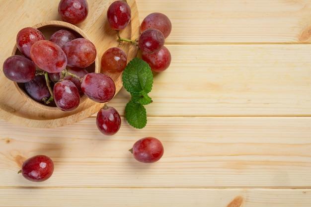 Cachos de uvas vermelhas maduras frescas na superfície de madeira.