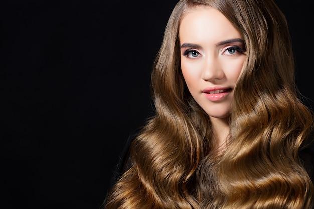 Cachos dourados luxuosos, retrato de uma mulher jovem e bonita com cabelo bonito, cópia de fundo preto com espaço à esquerda