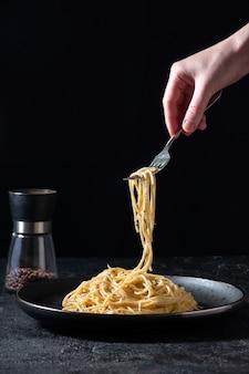 Cacio e pepe - massa italiana quente com queijo e pimenta no prato preto, mulher segurando o garfo com espaguete no escuro