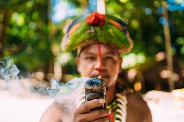 Cacique índio da tribo pataxó fumando cachimbo. índio brasileiro com cocar de penas e colar olhando para a câmera