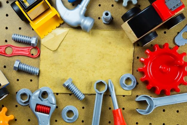 Caçoa ferramentas dos brinquedos da construção, ferramentas coloridas do brinquedo, construção no fundo de madeira.