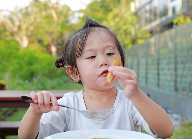 Caçoe a menina que come à mão no jardim.