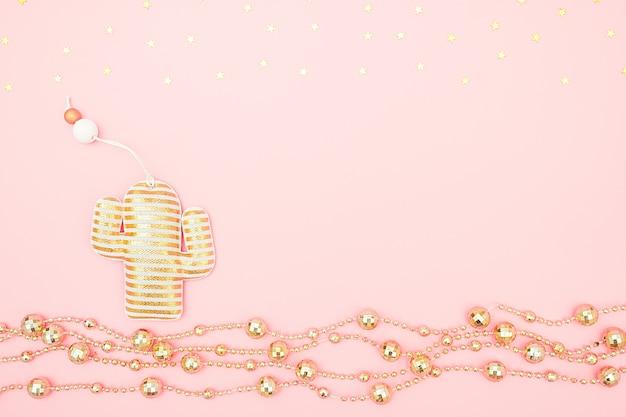 Cacto de brinquedo de natal de têxteis decorativos, festão dourada e estrelas no conceito de noite de natal tropical rosa ou ano novo.