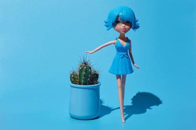 Cacto em um pote azul sobre fundo azul. a boneca toca as agulhas de um cacto. foto sob luz solar intensa.