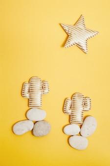 Cacto listrado dourado em seixos marinhos redondos e estrela dourada