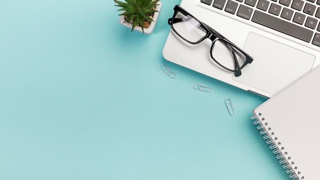 Cacto planta, clipes de papel, óculos, bloco de notas em espiral perto do laptop