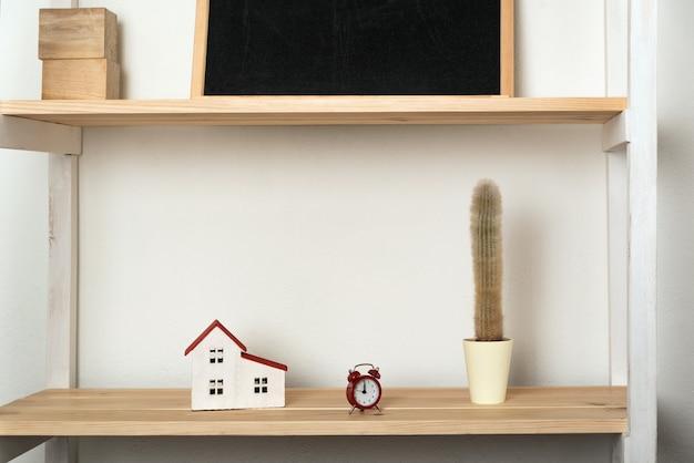 Cactus, casa modelo e despertador retrô na prateleira de madeira. decoração interior em cores claras.