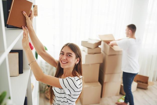 Cada livro deve estar no lugar certo. casal jovem alegre em seu novo apartamento. concepção de movimento.