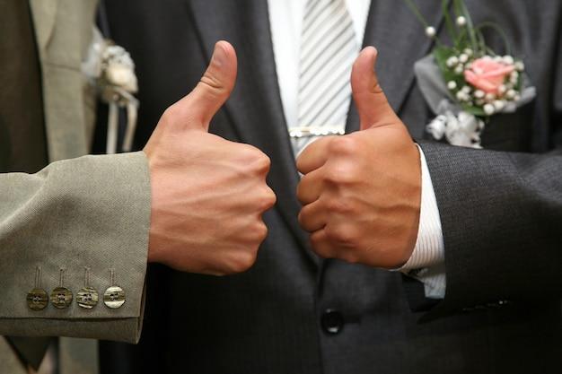 Cada noiva e noivo levantam as mãos com o polegar para cima