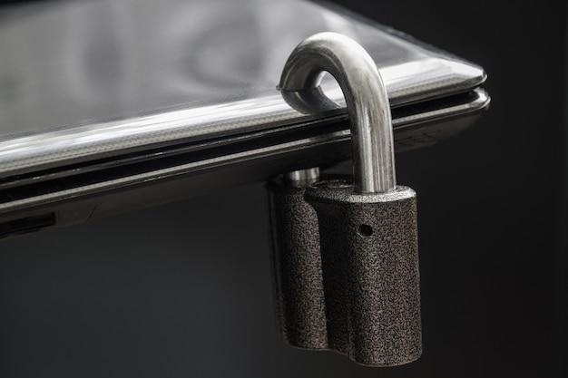 Cadeado de aço trancado em um orifício do laptop preto em fundo escuro
