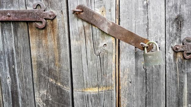 Cadeado de metal vintage velho em uma porta de madeira fechada de uma antiga casa de fazenda. o verdadeiro estilo da aldeia. fechar-se. concentre-se no castelo. fundo de madeira, textura. copie o espaço.