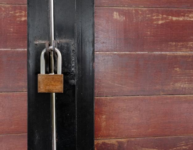 Cadeado dourado na velha porta de madeira
