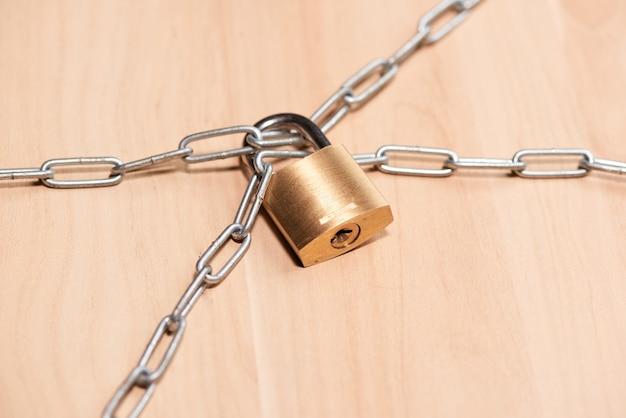 Cadeado e corrente na mesa de madeira. proteção de conceito.