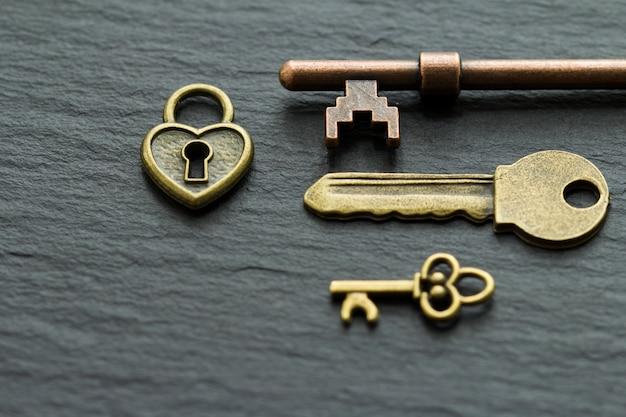 Cadeado em forma de coração com chaves em uma pedra ardósia