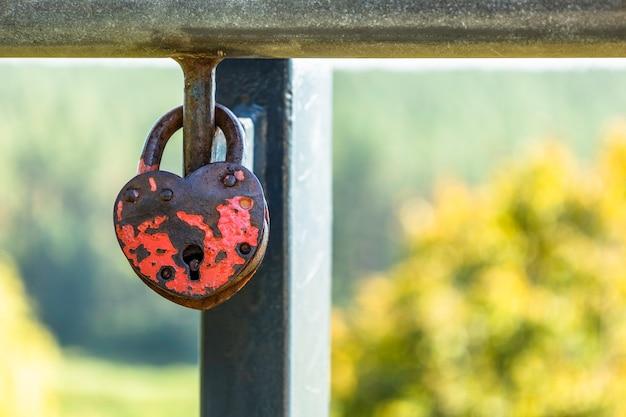 Cadeado em forma de coração pendurado em trilhos entre outros cadeados variados.