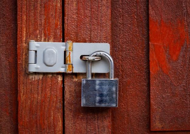 Cadeado fechado com corrente no fundo da porta de madeira vermelha, vintage