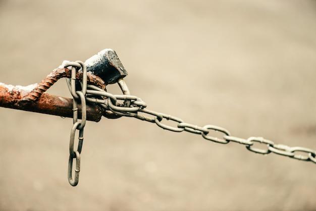 Cadeado fechado na cadeia de cerca marrom é close-up no fundo do asfalto com bokeh com espaço de cópia