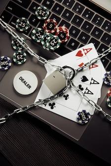Cadeado, jogando fichas e cartas no teclado do laptop. conceito de lei e regulamentação do jogo