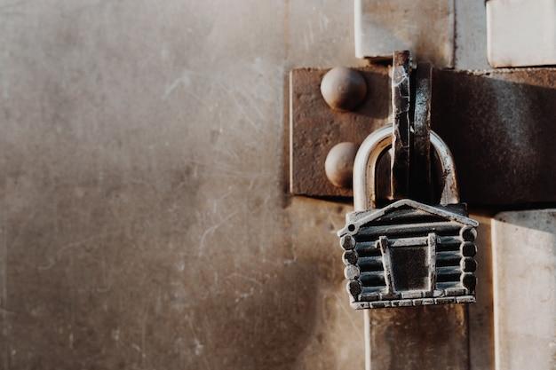 Cadeado na forma de uma cabana paira sobre as dobradiças do portão fechado. portões de metal.