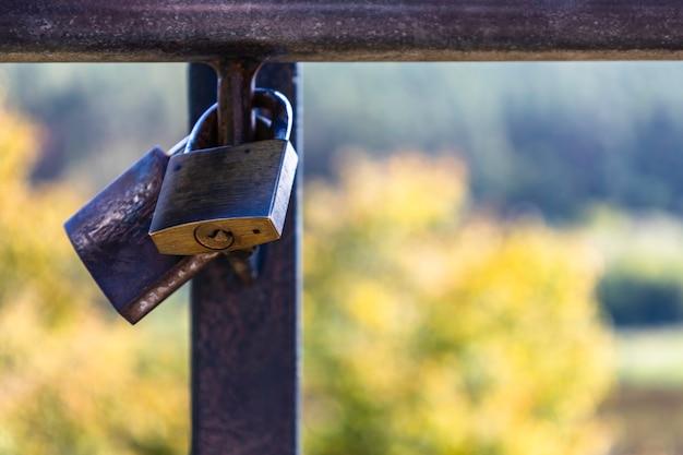 Cadeados do amor pendurados no corrimão, entre outros cadeados do amor variados.