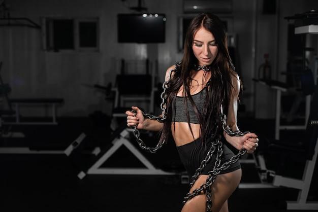 Cadeia de elevação feminino fisiculturista, garota fitness posando em cadeias