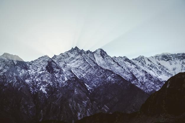 Cadeia de montanhas cobertas de neve com um céu claro ao pôr do sol