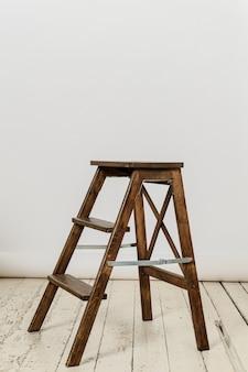 Cadeira alta de escada de madeira na parede fotográfica branca no piso de madeira branco