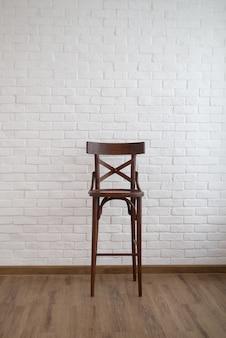 Cadeira alta de madeira marrom escuro com design de interiores de decoração de parede de tijolo branco