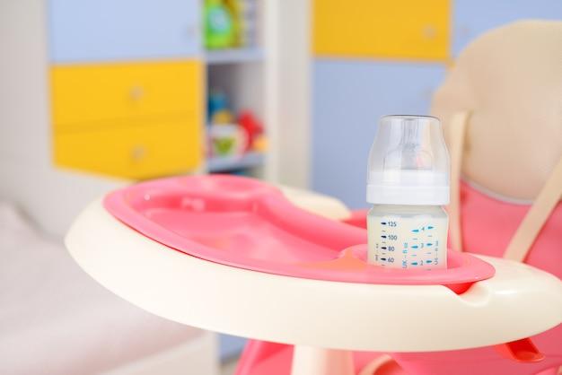 Cadeira alta rosa bebê e mamadeira com leite no quarto do bebê