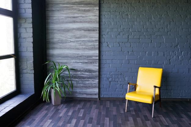 Cadeira amarela perto da janela no interior escuro moderno com parede de tijolo preto, cópia espaço