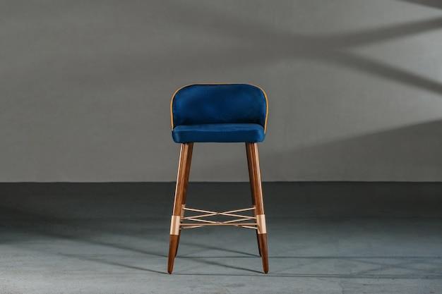 Cadeira azul da sala de jantar em um estúdio com paredes cinza