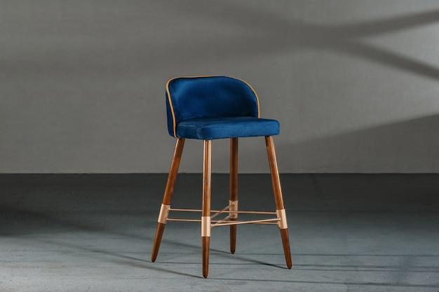 Cadeira azul da sala de jantar em uma sala com paredes cinza