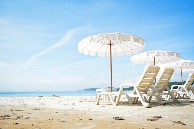 Cadeira branca com guarda-sol na praia à beira-mar